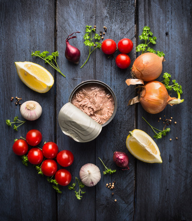 overhead view: canned  tuna fish and ingredient for tomato sauce with herb, spices and lemon on blue wooden background, top view