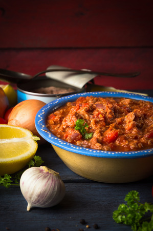 sause: Tomato sause with tuna fish on rustic kitchen table with vegetables Stock Photo