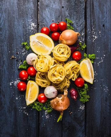 乾燥パスタ トマト、ハーブ、トマトソース、暗い青色の背景、トップ ビューで comosing のためのスパイスのタリアテッレ
