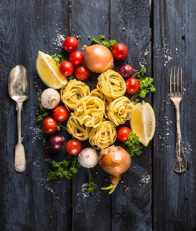 italy background: pasta tagliatelle with tomatoes, vegetables and spices for tomato sauce,spoon and fork on dark blue wooden background, top view