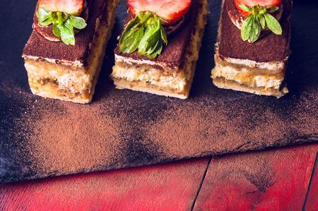 Drei Tiramisu Kuchen auf schwarzem Schiefer und rote Holzuntergrund
