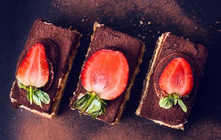 eating cake: chocolate  tiramisu cake with strawberries on black slate, top view