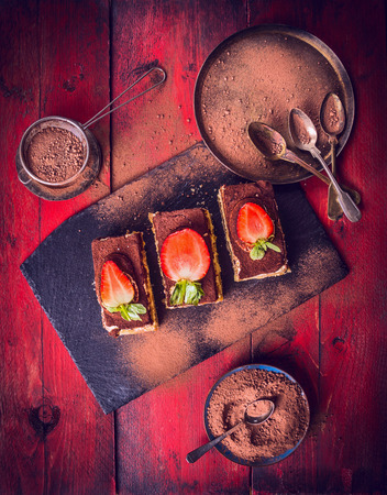 composing: tiramisu with strawberries and Chocolate powder, composing on red wooden background, top view