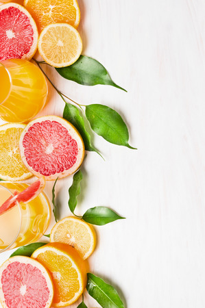 mandarin oranges: Citrus fruits with green leaves and glass with juice on white wooden table, frame with place for text Stock Photo