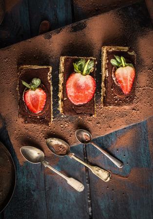 composing: three tiramisu cake with strawberries and spoons on dark blue wooden background