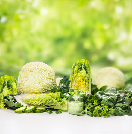 Green vegetables and glass smoothie with over blurred nature background