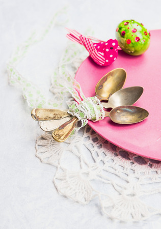 Old spoon with a ribbon on a pink plate with Easter egg photo