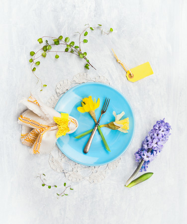 hyacinths: Blue plate with spring flowers, fork, sign and decoration on gray wooden background, top view