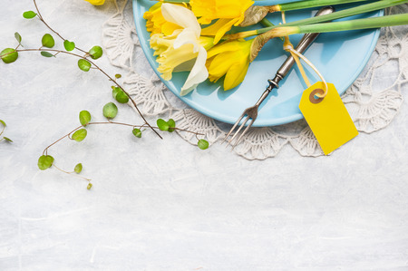 Yellow daffodils on blue plate with fork and table sign, spring decoration, top view, frame Stock Photo