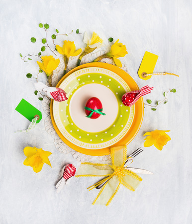Easter table decoration with red egg, spring flowers, sign, knife and fork on yellow plate, top view