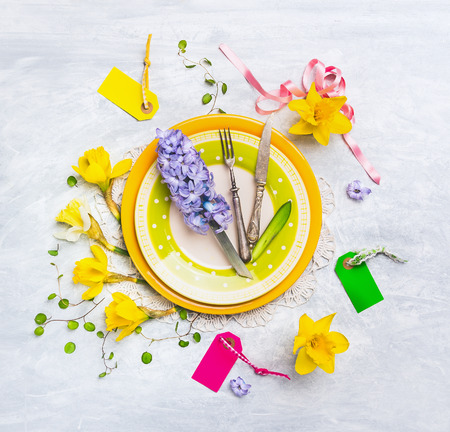 hyacinths: Spring table decoration with with narcissus, hyacinths, sign, ribbons, knife and fork on green plate, top view Stock Photo