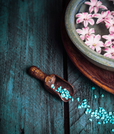 still life: Wooden scoop with blue sea salt and bowl with water and flowers, spa wellness background Stock Photo