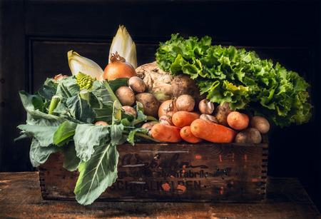 various of fresh vegetables in old box over dark wooden wall Foto de archivo