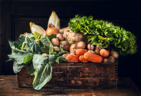 various of fresh vegetables in old box over dark wooden wall Stockfoto