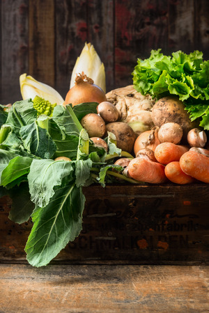 Organic vegetables box on old wooden background photo