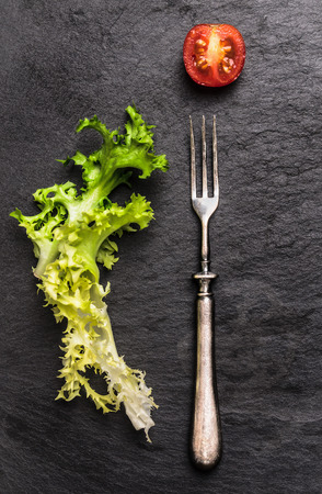 Fork, salad leaves and tomato on slate, simple food background, top view photo