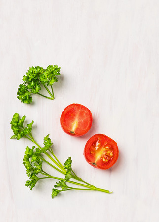 Simple food background, parsley and tomato on white wooden table Foto de archivo