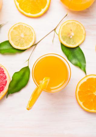 감귤 류와 녹색의 조각으로 오렌지 주스 유리 나뭇잎에 흰색 나무 배경, 상위 뷰