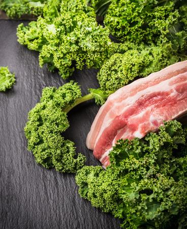 perishable: Kale and Raw Pork brisket on slate background Stock Photo