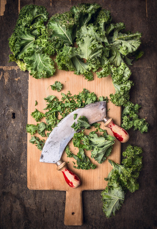 mincing: kale on cutting board chopping and mincing knife old, dark wooden background, top view Stock Photo