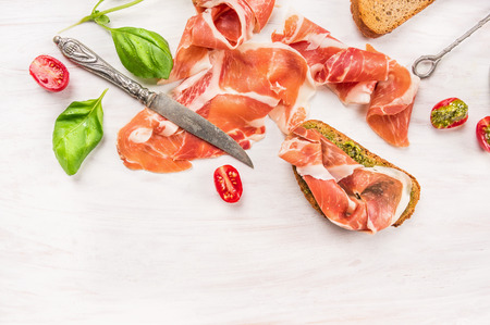ham with toast, knife, Basil and pesto on white wooden background, top view