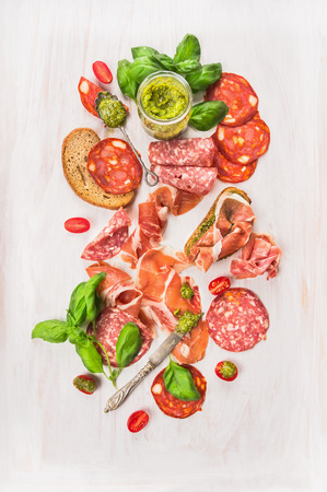 Cold Italian meat plate with ham, sausage, bread and pesto on white wooden background, top view