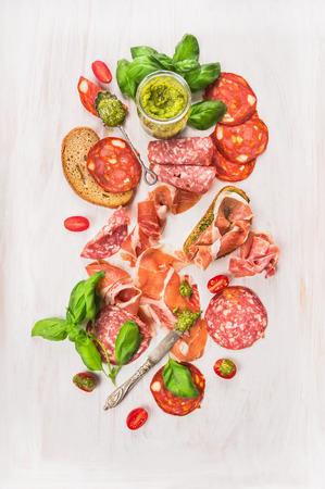embutidos: Fría plato de carne italiana con jamón, salchichas, pan y pesto sobre fondo de madera blanco, vista desde arriba