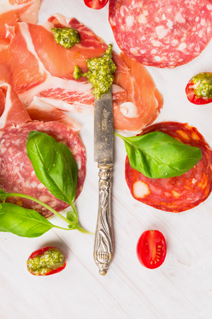 Different Italian sausage and ham with basil pesto and knife on white wooden background photo