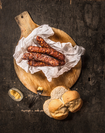 top down: German smoked sausage on round cutting board with bread, mustard and beer, top view