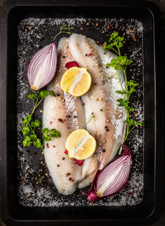 white backing: Raw fish with spices, herb, helped onion, lemon and salt on dark backing tray background, top view Stock Photo