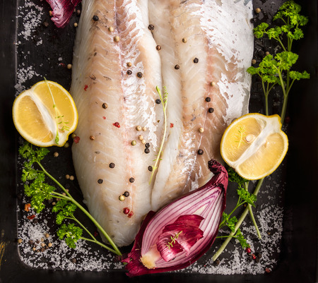 backing: raw zander fish fillet on backing tray with lemon, herbs and red onion, top view