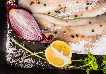 white backing: Raw fish fillet with red onion, half lemon, salt, herbs and spices on dark background, top view Stock Photo