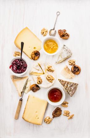queso de cabra: diversos tipos de queso con salsa, nogal y los higos en el fondo de madera blanca