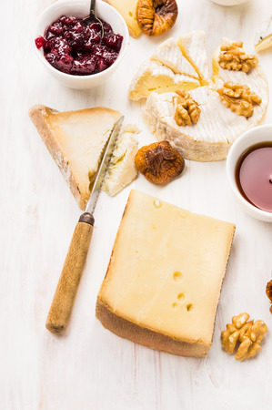 r sliced: various cheese with dip and walnut on white wooden background