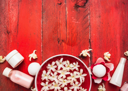 creme: Red wellness background: bowl with white flowers in water, creme and lotion bottle on red wooden table, top view Stock Photo