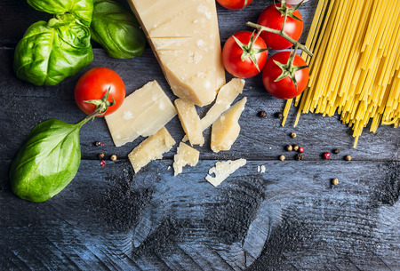 light meal: Ingredients for spaghetti with tomato sauce: basil, tomatoes, parmesan cheese on blue wooden background, top view, place for text