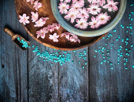Schep met zeezout kom en bloemen in het water op blauwe houten tafel, SPA achtergrond, bovenaanzicht