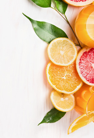 Citrus juice and sliced ?????????? fruits: orange, lemon and grapefruit on white wooden background Stock Photo