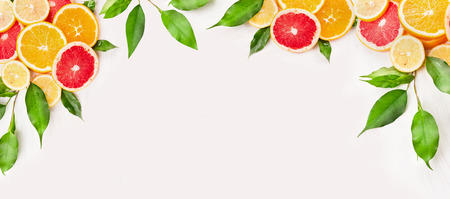 Citrus fruits slice with green leaves on white wooden background, banner for website