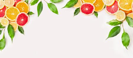 citricos: Los c�tricos rebanada con hojas verdes sobre fondo de madera blanca, la bandera para el sitio web Foto de archivo