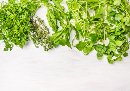 herbs mix for salad and courses on white wooden background with place for text photo