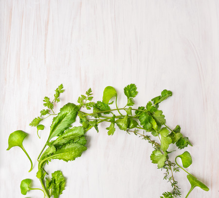 balm: green herbs on white wooden table, food background, top view