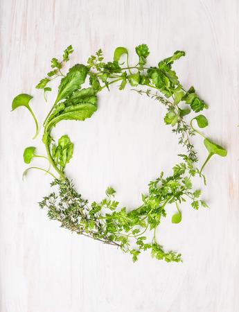 wreath of green herbs: thyme, coriander, parsley, mustard, marjoram , oregano, chervil , Cuminum , watercress , savory on white wooden background, top view