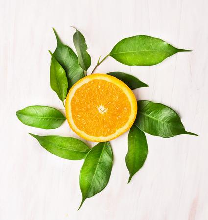 Naranja lóbulo con hojas verdes en la mesa de madera blanca, vista superior Foto de archivo - 36950085