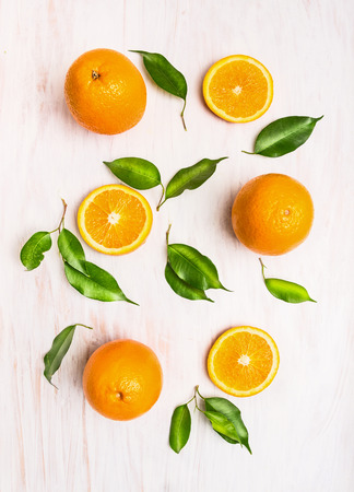 Orange fruits composition with green leaves and slice on white wooden background, top view Stockfoto