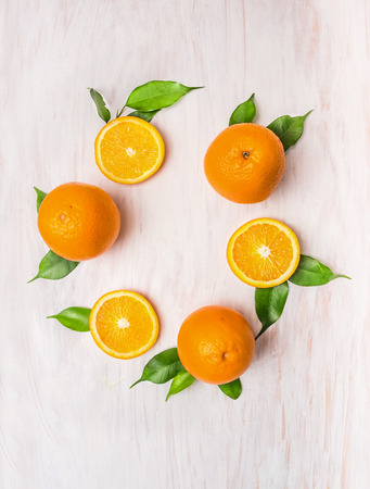 orange slices: Orange fruits with leaves wreath on white wooden background, top view