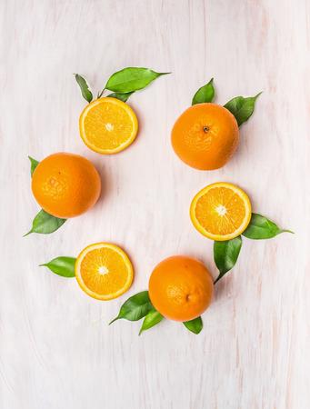 Oranje vruchten met bladeren krans op witte houten achtergrond, bovenaanzicht