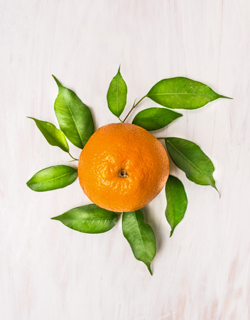 orange fruits with green leaves on white wooden background, top view Stock Photo