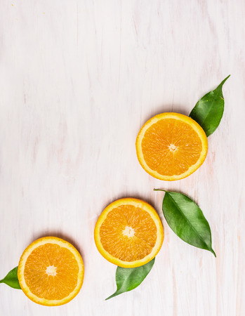 cutting orange fruits with leaves on white wooden background with copy space, top view Standard-Bild