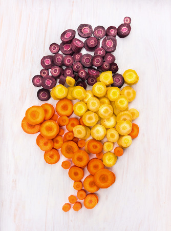 vegetus: multicolored chopped carrots on white wooden table, top view Stock Photo